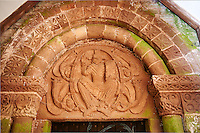 Norman Romanesque arch and tympanum of the south doorway of the church of St Peters, Rowlstone, Herefordshire, England. The arch has rolled mouldings which is framed by a thin row of chip-carved triangles. Inside is a relief sculpture of Christ Pantocrator or Christ in Majesty. This design is typical of the prevailing iconography used in the eastern Roman Byzantine Empire. Christ is depicted in an oval mandorla which was used in the Byzantine Eastern Orthodox Church to represent a moment which transcends time and space, such as the Resurrection. The mayoral is being supported by flying angels. The face of Jesus Christ's was removed either in the reformation or by Puritans after the English Civil War.