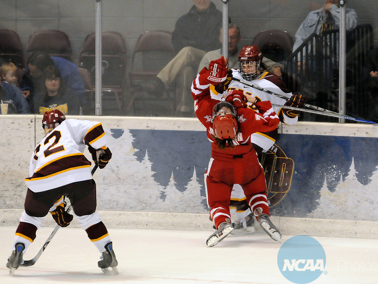 22 MAR 2008: Right wing Meghan Duggan (7) of the University of Wisconsin is knocked down by defender Myriam Trepanier (81) of the University of Minnesota Duluth (UMD) during the Division I Women's Ice Hockey Championship held at the Duluth Entertainment Convention Center in Duluth, MN. Trepanier was called for high sticking on the play. The University of Minnesota Duluth defeated the University of Wisconsin 4-0 to win the National title. Tom Dahlin/NCAA Photos.