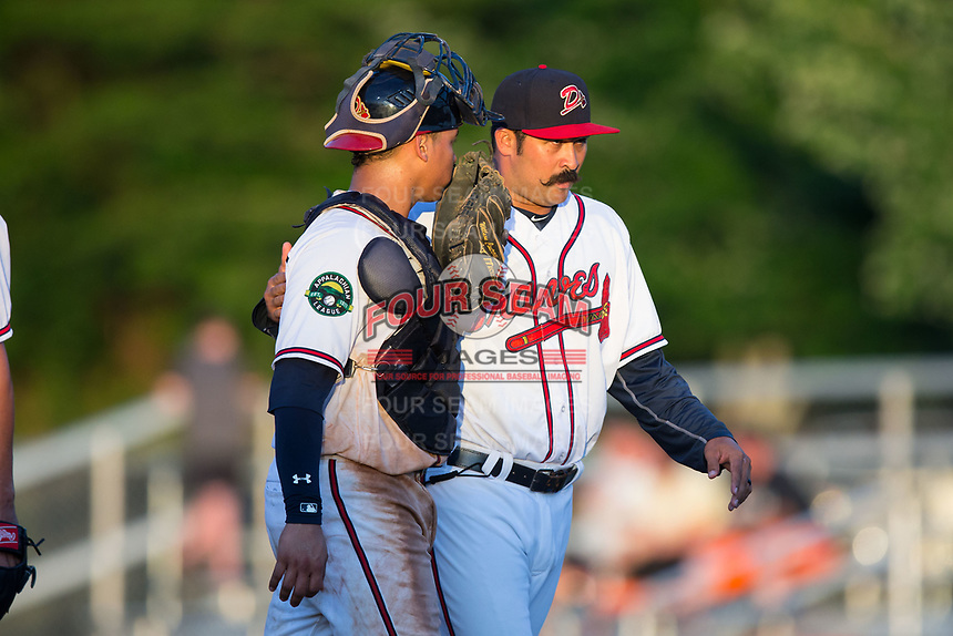 Danville Braves pitching coach Kanekoa Texeira (50) has a chat with catcher William Contreras (24) as he walks off the field during the game against the Princeton Rays at American Legion Post 325 Field on June 25, 2017 in Danville, Virginia.  The Braves walked-off the Rays 7-6 in 11 innings.  (Brian Westerholt/Four Seam Images)