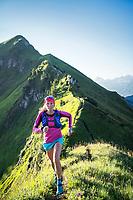 A woman trail running on the Rophaien ridgeline, Switzerland