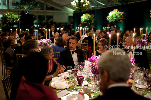 Washington, DC - November 24, 2009 -- Mrs. Gursharan Kaur, the wife of Prime Minister Manmohan Singh, talks with President Barack Obama during the State Dinner at the White House, November 24, 2009. Speaker of the U.S. House Nancy Pelosi and former Secretary of State Colin Powell are seated at right..Mandatory Credit: Pete Souza - White House via CNP
