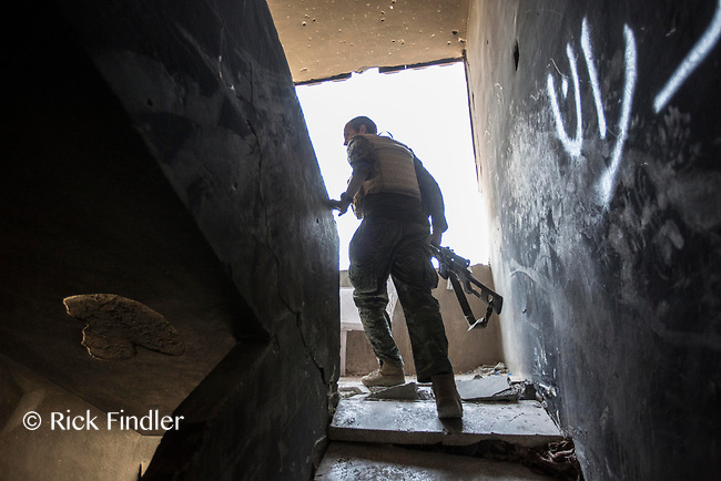 August 2017. Raqqa, Syria.<br /> Foreign volunteer fighter 'Macer Gifford', aged 30 and originally from Cambridgeshire, walks up the stairs of an abandoned building as he tries to locate a spot to fire his sniper rifle toward ISIS positions.<br /> The MFS (Syriac Military Council) are a group of Assyrian Christians who fight alongside the Syrian Democratic Forces in the fight to topple ISIS.<br /> Photographer: Rick Findler
