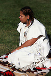 Native American Indian woman sitting on a blanket adjusting her leather dress