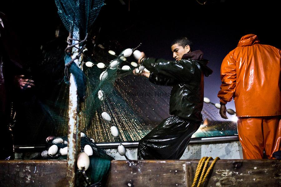 Gaza sea: a young fisherman pull out the net during the second session of the fishing time.<br /> <br /> Mer de Gaza: un jeune p&ecirc;cheur tire le filet pendant la deuxi&egrave;me session de la nuit de p&ecirc;che.