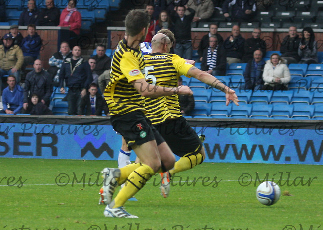 Dean Shiels (hidden) gets his shot away to score before being tackled by Daniel Majstorovic (5) and Charlie Mulgrew in the Kilmarnock v Celtic Clydesdale Bank Scottish Premier League match played at Rugby Park, Kilmarnock on 1.10.11