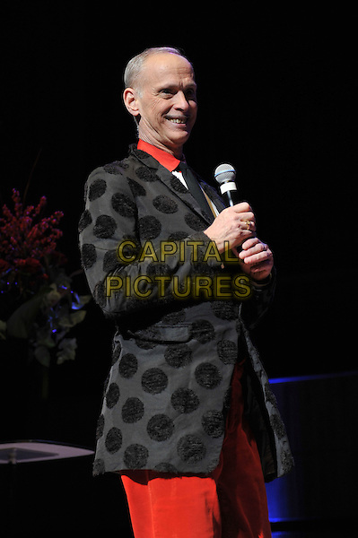 John Waters performing his one man show, 'A John Waters Christmas', Royal Festival Hall, London, England. .5th December 2011.stage concert live gig performance red trousers black polka dot jacket microphone half length side .CAP/MAR.© Martin Harris/Capital Pictures.