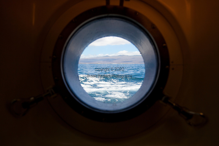 The view through a porthole from inside a small tour ship in the Galapagos of the water and the island