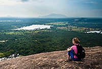 Woman sitting on Pidurangala Rock, looking at the jungle landscape of North Central Province, Sri Lanka. This is a photo of a woman sitting on Pidurangala Rock, looking at the jungle landscape of North Central Province, Sri Lanka.