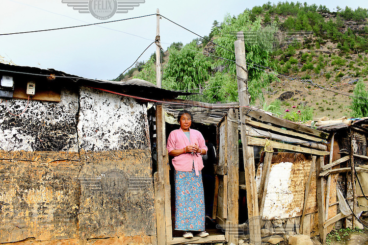 A woman stands outside her shack in the kala bazaar slum.