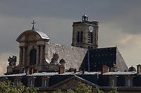 The top of the front of the Saint Gervais church (XVI-XVII century), with its roof, its statues and its bell tower, which rises among the surrounding buildings, as view from the Arcole bridge, in Paris. There was a typical beautiful Parisian sky with sun and clouds. Digitally Improved Photo.