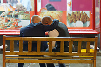 Pictured: Two men have a meal on a bench outside a take-away in Wind Street, Swansea, south Wales, UK. Friday 21 December 2018<br /> Re: Black Eye Friday, also known as Mad Friday or Black Friday which is the last Friday before Christmas Day.
