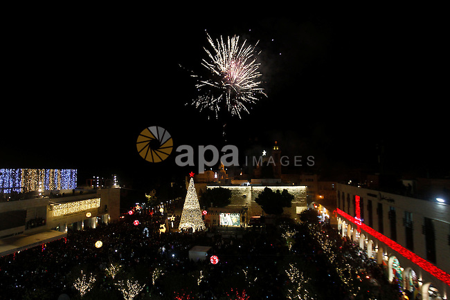 Palestinian Christians watch fireworks marking the lighting of a Christmas tree on December 3, 2016 at the Manger Square near the Church of the Nativity, revered as the site of Jesus Christ's birth, in the biblical West Bank town of Bethlehem. Photo by Wisam Hashlamoun