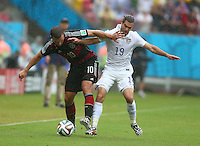 Lukas Podolski of Germany and Graham Zusi of USA in action
