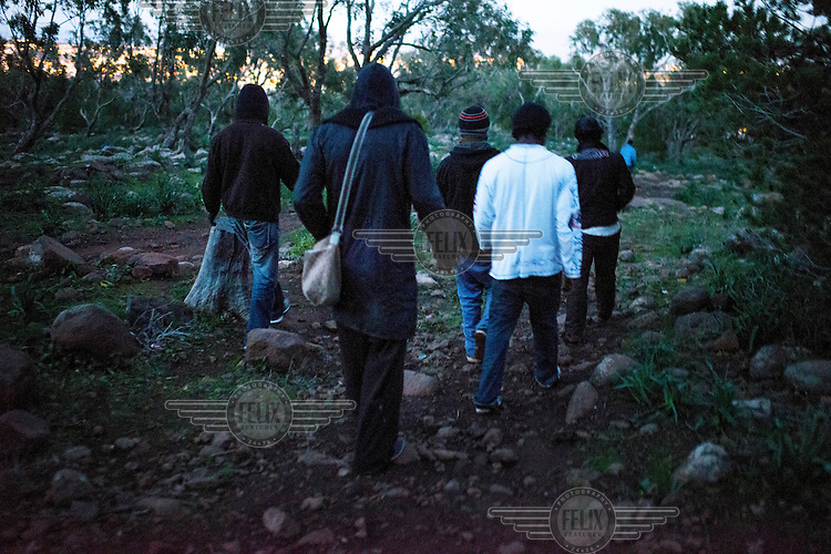 A group of migrants from Sub-Saharan Africa walking in the Gurugu Mountains where about 1200 migrants have set up a camp deep in a forest, hidden from the police and authorities. The camp is near the Spanish exclave of Melilla and many of the migrants try to break into the city in hope of eventually finding a way to enter Europe.