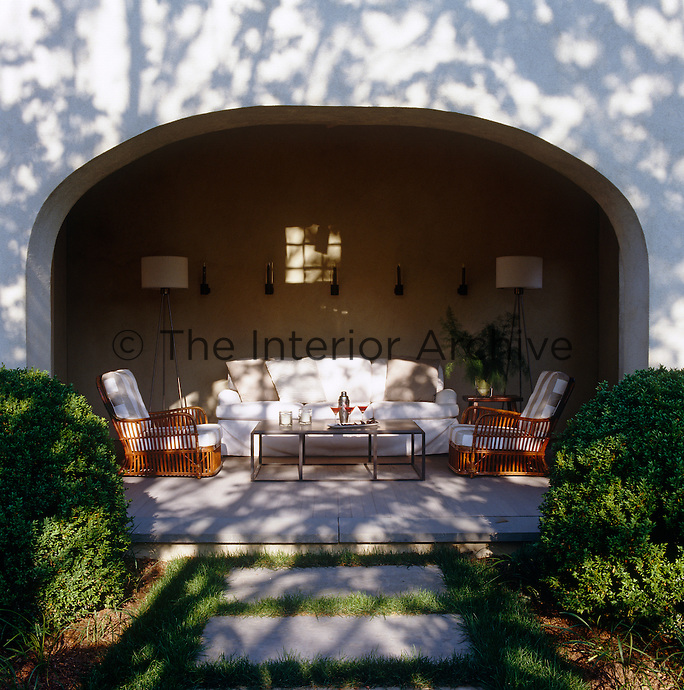 The covered porch becomes an outdoor living room in the summer; the sconces and floor lamps are Greg Yale designs and the chairs are 1920s rattan