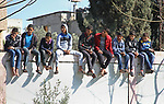 Palestinian fans sit on a wall as they attend the football match between Shabab Jabalia football club (in yellow) and al-Hilal football club (in black) at Beit Lahia Stadium in the northern Gaza Strip on March 11, 2018. Photo by Mahmoud Ajour