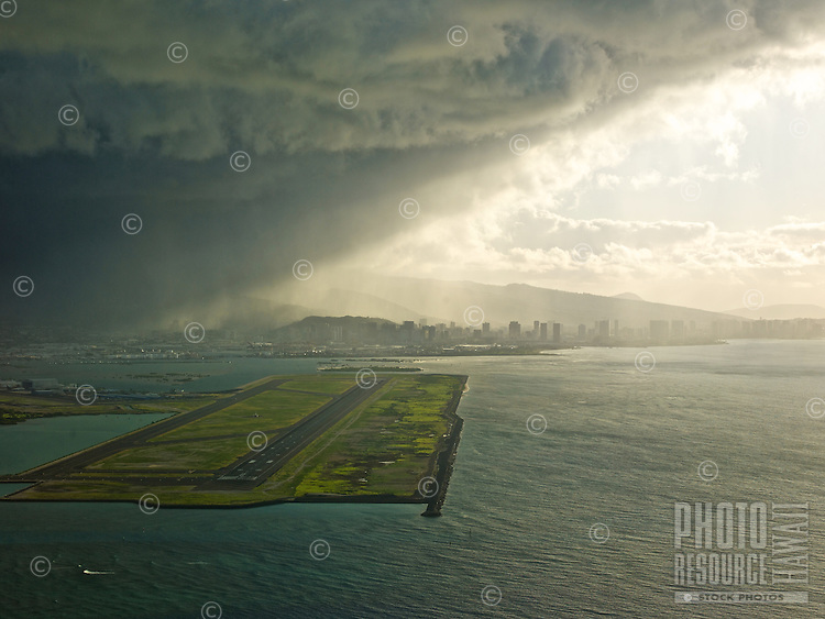 An aerial view of a storm cloud passing over the Reef Runway at Honolulu International Airport, Honolulu, O'ahu.
