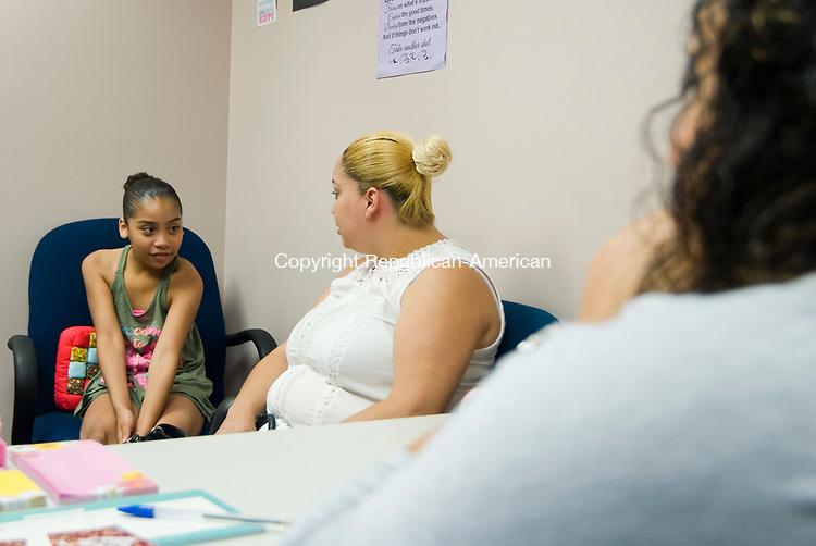 WATERBURY, CT-0712117JS02--Charitza Santiago talks with her daughter Amariz Rosso, 10, in the office of Natalie Rosado during a meeting Friday at the Hispanic Coalition in Waterbury. The two are victims of the Lounsbury Street fire that displaced 37 people.  Allied Automotive will be hosting a car show on August 19, at Lakewood Park in Waterbury where money raised will be donated to the Hispanic Coalition for the victims. <br /> Jim Shannon Republican-American
