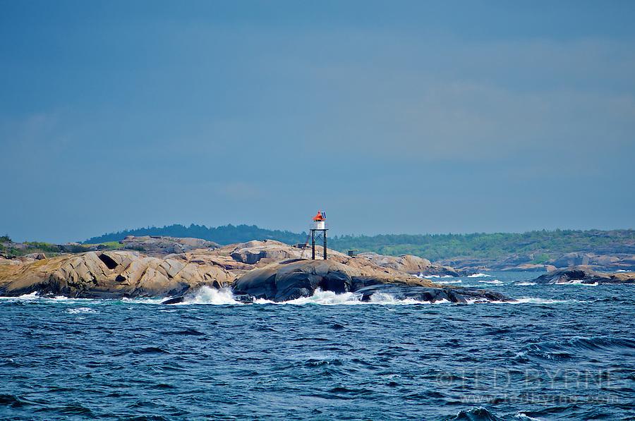 Rugged coastline and warning signal in Norwegian Fjord (Sandefjord)