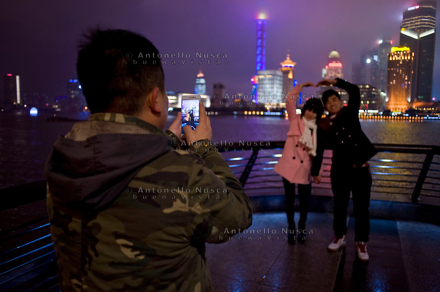 Turisti cinesi in posa per una foto sul Bund. Chinese tourists pose for photos on the Bund in downtown Shanghai