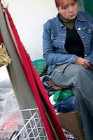 Woman shopkeeper at farmers market taking a moment and looking sad in Poland. Rawa Mazowiecka Central Poland
