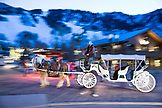 USA, Colorado, Aspen, a horse and carriage walk through the square in downtown Aspen at dusk