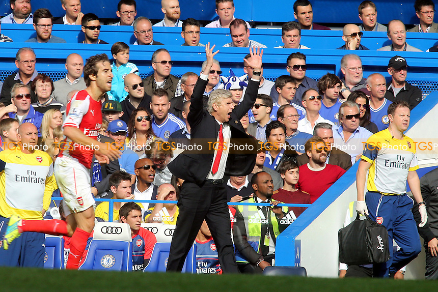 Arsenal Manager, Arsene Wengar, gets frustrated with a decision and walks towards Jose Mourinho  - Chelsea vs Arsenal - Barclays Premier League Football at Stamford Bridge, London - 05/10/14 - MANDATORY CREDIT: Paul Dennis/TGSPHOTO - Self billing applies where appropriate - contact@tgsphoto.co.uk - NO UNPAID USE