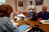 United States President George W. Bush reads over paperwork during a White House staff meeting inside a telecommunications trailer at the Bush Ranch in Crawford, Texas, Friday, August 9, 2002. From left are Staff Secretary Harriet Miers, personal assistant Blake Gottesman and Deputy Chief of Staff Joe Hagin. <br /> Mandatory Credit: Eric Draper - White House via CNP
