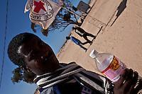 Tunisie RasDjir Camp UNHCR de refugies libyens a la frontiere entre Tunisie et Libye refugees camp  Tunisian and Libyan border  Tunisia campo profughi di Djiba al confine tra tunisia e Libia  refugie avec une bouteille d eau  rifugiato tiene in mano una bottiglia d'acqua, sullo sfondo bandiera della croce rossa internazionale