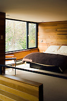 The walls of the open plan bedroom on the mezzanine echo the cedar wood panelling which has been used to line the walls throughout the property