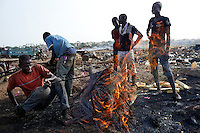 ACCRA, GHANA APRIL 19: Men work at Agbogbloshie, a <br /> Huge recycling area on April 19, 2015 in central Accra, Ghana. Everything is recycled and bartered here. Most popular are recycled e-waste and car parts.  It has been called an e-waste dumping ground. (Photo by: Per-Anders Pettersson)