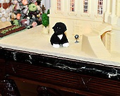 Bo rests in front of the traditional White House ginger bread house is displayed on the eagle-pedstal side table of the State Dining Room in Washington, DC.  It weighs approximately 400 pounds and took almost 2 months to make. It is an accurate replica of the White House.  The theme for the White House Christmas 2011 is Shine, Give, Share - celebrating the countless ways we can lift up those around us, put our best self forward in the spirit of the season, spend time with friends and family, celebrate the joy of giving to others, and share our blessings with all.  The theme translates to the holiday décor on several levels. There is the literal translation through the use of shiny elements – star motifs, quartz and metallics like copper, aluminum and mirrored paper. There is also a conceptual connection – we're inviting visitors to give their thanks to members of our military, and have once again invited guest artists to share their talents working with the White House. This year's décor also includes handmade decorations crafted from simple materials – paper, felt, and even recycled cans. These are projects that anyone can do at home using readily available materials that are inexpensive or free..Credit: Ron Sachs / CNP