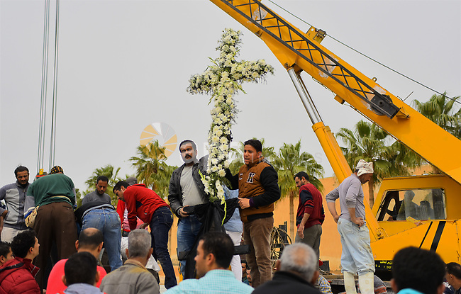 Egyptian workers use crane to lift coffins of the victims of the blast at the Coptic Christian Saint Mark's church in Alexandria the previous day during a funeral procession at the Monastery of Marmina in the city of Borg El-Arab, east of Alexandria on April 10, 2017. Egypt prepared to impose a state of emergency after jihadist bombings killed dozens at two churches in the deadliest attacks in recent memory on the country's Coptic Christian minority. Photo by Amr Sayed