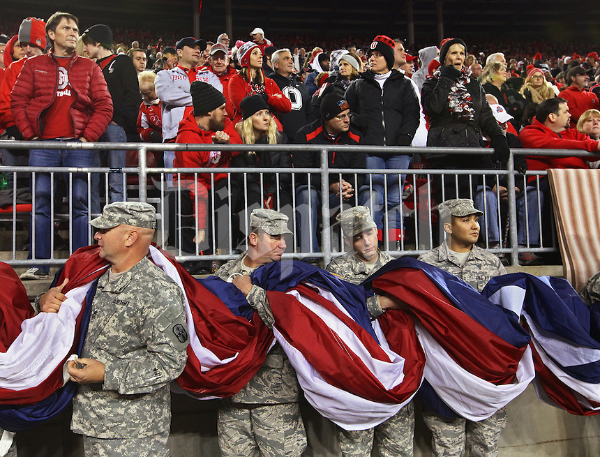 Soldiers hold a giant American flag before taking it on the field for the National Anthem before an NCAA football game between the Ohio State Buckeyes and the Minnesota Golden Gophers at Ohio Stadium on Saturday, November 7, 2015. (Columbus Dispatch photo by Fred Squillante)