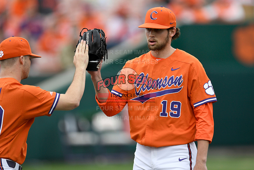 Starting pitcher Brooks Crawford (19) of the Clemson Tigers is greeted after pitching a scoreless inning of a game against the South Alabama Jaguars on Opening Day, Friday, February 15, 2019, at Doug Kingsmore Stadium in Clemson, South Carolina. Clemson won, 6-2. (Tom Priddy/Four Seam Images)