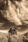 Sepia toned image of old outhouse with dramatic clouds in the sky