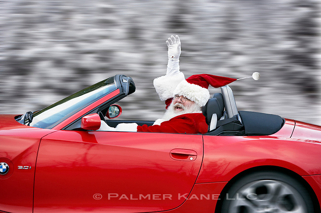 Santa claus behind the wheel of a flashy new convertible in the snowy woods