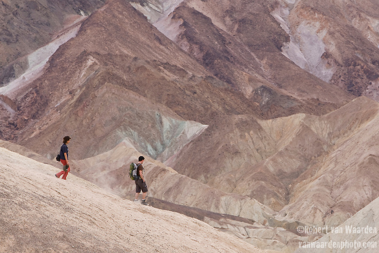 A man and a woman hike the hills of Death Valley National Park as seen from Zabrieskie Lookout, Nevada, United States of America.