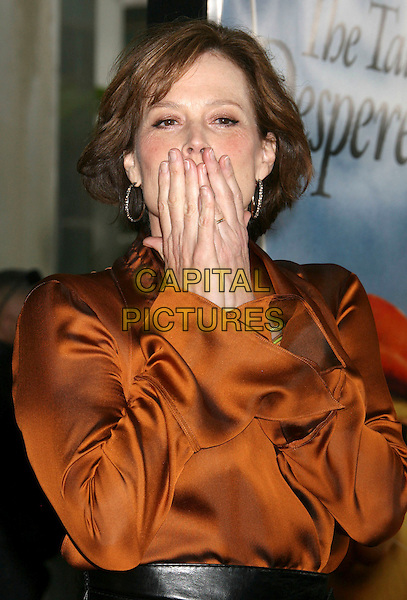 "SIGOURNEY WEAVER.""The Tale Of Despereaux"" World Premiere held at the Arclight Hollywood Cinemas, Hollywood, California, USA..December 7th, 2008.half length orange top black waist belt blouse brown hands covering face blowing kiss .CAP/ADM/MJ.©Michael Jade/AdMedia/Capital Pictures."