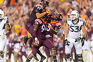 Landover, MD - SEPT 3, 2017: Virginia Tech Hokies defensive end Vinny Mihota (99), Virginia Tech Hokies defensive end Trevon Hill (94) and Virginia Tech Hokies running back Deshawn McClease (33) celebrate his interception during game between West Virginia and Virginia Tech at FedEx Field in Landover, MD. (Photo by Phil Peters/Media Images International)