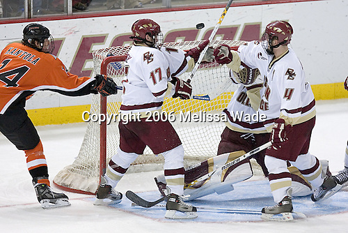 Both Joe Rooney 17 and Mike Brennan 4 of Boston College reach in to help Cory Schneider 1 keep the airborne puck out of the net and away from Kai Kantola 14 of Bowling Green. The Eagles of Boston College defeated the Falcons of Bowling Green State University 5-1 on Saturday, October 21, 2006, at Kelley Rink of Conte Forum in Chestnut Hill, Massachusetts.<br />