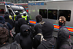 """© Joel Goodman - 07973 332324 . 26/03/2011 . London , UK . A black bloc of protesters carrying black and red anarcho-syndiclist flags spray a police van with graffiti . Hundreds of thousands of people attending an anti cuts demonstration under the banner """" March for the Alternative """" in central London , in protest at the coalition government's austerity measures . Photo credit : Joel Goodman"""