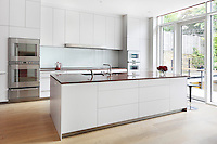 A light and modern Bulthaup 'Lipton' kitchen with white units and red granite work surfaces