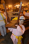 Donggang, Taiwan -- Young helper carrying a bench at Donglong Temple.