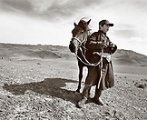 MONGOLIA, shehperd Batsuuriin stands with his horse Khaltar and watches his lifestock, the Gobi Desert, Nemegt Basin (B&W)
