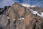 Man pauses on a rock ledge while looking at East Face of Longs Peak, Rocky Mtn Nat'l Park, CO