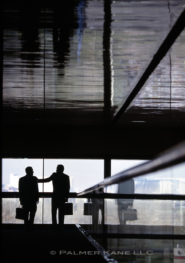 Silhouettes of business men talking in hallway