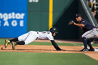 Yoan Moncada (10) of the Charlotte Knights dives back into first base as Matt Tuiasosopo (5) awaits a pick-off throw at BB&T BallPark on July 16, 2017 in Charlotte, North Carolina.  The Knights defeated the Braves 5-4.  (Brian Westerholt/Four Seam Images)