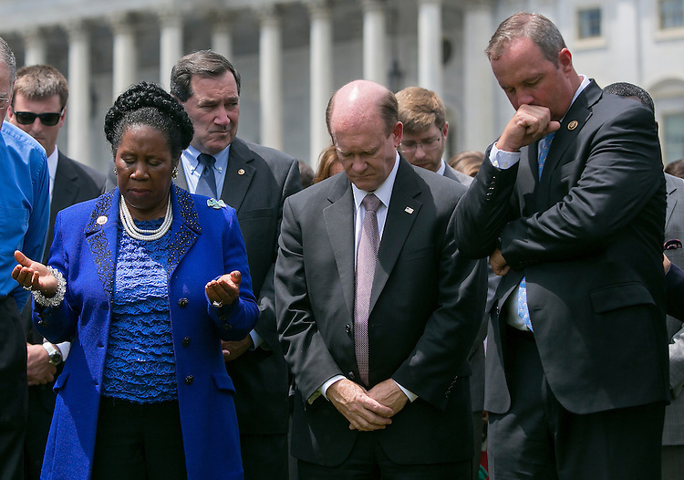 UNITED STATES - JUNE 18 - From left, Rep. Sheila Jackson Lee, D-Texas, Sen. Chris Coons, D-Del., and Rep. Jeff Duncan, R-S.C., pray during a vigil for victims of the Charleston shooting, outside of the U.S. Capitol on Thursday, June 18, 2015. (Photo By Al Drago/CQ Roll Call)
