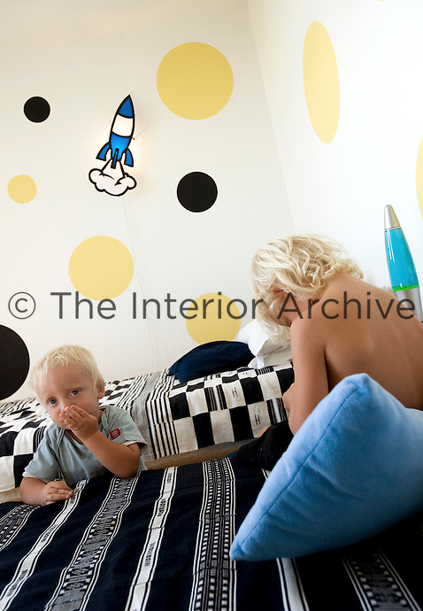 Two boys are playing in their bedroom which features a fun mural with a painted rocket ship